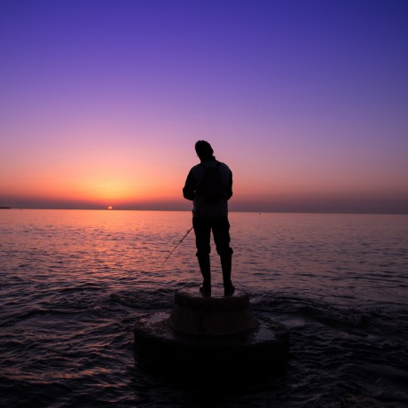 The lonely fisherman at the rising of the sun